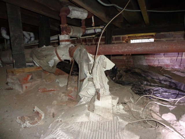 Old deteriorated asbestos at drain piping.